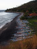 Parked Fishing Boats on the Beach, Amed, Bali. Long line of parked wooden fishing boats on the black sand beach in Amed, Bali, Indonesia stock photography