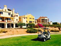 Golf in Spain with buggy in front of holiday houses and palm threes around. Parked golf buggy on fairway in front of holiday houses in Spain with clear blue sky Stock Images