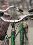 Parked green bike. Close up of green bike on bicycle park on gloomy rainy day Stock Image