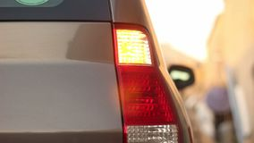 Parked car. Right direction indicator light from back is on. Parked hatcback or SUV car. Right direction indicator light from back is on stock footage