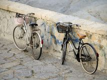 Italian street scene. Two bikes parked by stone wall. Two old fashioned Dutch style ladies' bicycles with baskets parked against a stone wall in Bordighera Stock Photo