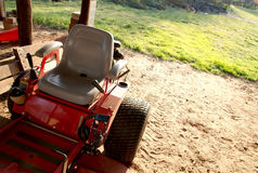 A parked lawnmower in a barn. A red parked lawnmower in a barn stock images