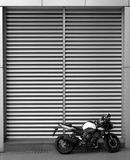 Parked motorbike by metal slats wall Royalty Free Stock Image