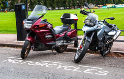 Parked Motorcycles infront of a city park Royalty Free Stock Photography