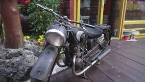 Parked old-fashioned vintage motorcycle black color. Standing on wooden floor stock video