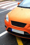 Parked orange sports car. Orange sports car parked at the kerb, front view Royalty Free Stock Photo