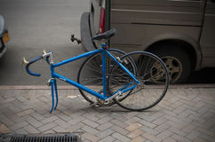 Parked racing bike. Locked blue racing bike with dismounted front wheel to prevent theft Stock Photo