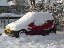 Parked red car under a layer of snow. A parked red car standing on a parking-place under a layer of snow Stock Images
