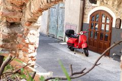 Parked red scooter. Red scooter parked in front of wooden door royalty free stock image