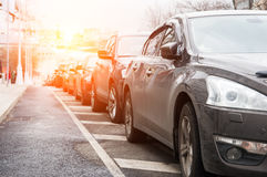 Parked in a row cars. On the roadway of the city street royalty free stock image