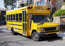 Parked School Bus. Front and side view of yellow-orange school bus parked in residential neighborhood Stock Photography