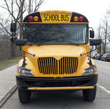Parked School Bus. Front view of parked school bus on city street Royalty Free Stock Images