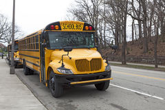 Parked School Bus. Side and front view of parked school bus on city street Stock Image