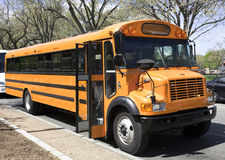 Parked School Bus. Side and front view of parked school bus on city street with door open Stock Image