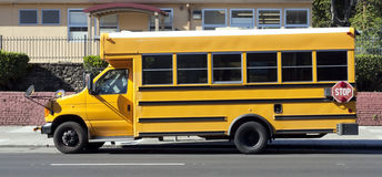 Parked School Bus. Side view of parked school bus on city street Stock Images