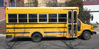 Parked School Bus. Side view of parked school bus on city street Royalty Free Stock Photos