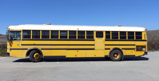 Parked School Bus. Side view of parked school bus in parking lot under blue sky Stock Photography