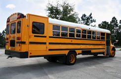 Parked schoolbus rear. Rear view of a Schoolbus parked in a parking lot Royalty Free Stock Images