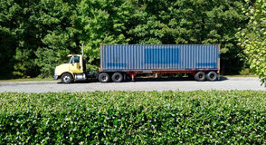 Parked Semi. Semi, cab, trailer parked along a row of trees with hedge in foreground Stock Photography