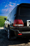 Parked SUV. A parked SUV on an old road with a view of green grass and a bright blue sky Stock Images
