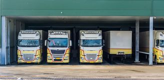 Parked trucks at a docking station of a warehouse, logistics and transportation background. Many parked trucks at a docking station of a warehouse, logistics and royalty free stock photography
