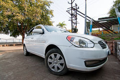 Parked white motor car. Low angle view of modern white motor car parked in on urban drive Stock Photography