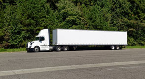 Parked White Semi. Cab and trailer in front of trees with road in foreground Royalty Free Stock Images