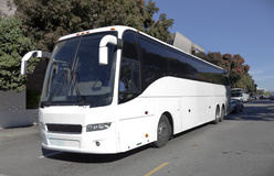 Parked White Tour Charter Bus. Side and front view of white tour charter bus in city traffic with blue sky Royalty Free Stock Photo