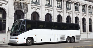 Parked White Tour Charter Bus. Side and front view of parked white tour charter bus in front of building Stock Photos
