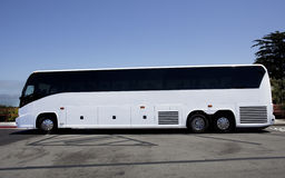 Parked White Tour Charter Bus. Side view of white tour charter bus in parking lot with blue sky Royalty Free Stock Photography
