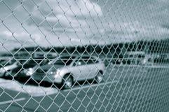Parkeerterrein achter veiligheidsomheining Stock Afbeelding