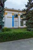 Parken Sie Gasse mit ordentlich befestigten grünen Büschen nahe einem schönen Gebäude mit dekorativen dekorativen Formteilen Stockfotografie
