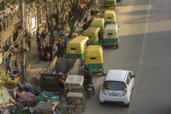 Parkende indische Rikschas nahe Mülleimern und Bürgersteigsvogelperspektive stockfotos