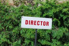 Parkendes Zeichen Direktors, rote Buchstaben, reservierter Platz, hinter gr?nem nat?rlichem Hintergrund stockfotos