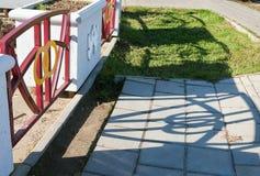 Parkera av det nyligen gift Ett staket med två skärande vigselringar och skuggor på jordningen Arkivbild
