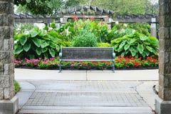 Parkera bänken, blommaträdgården, Eichelman parkerar, Kenosha, Wisconsin royaltyfri foto