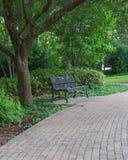 Parkera bänken och den Pavestone gångbanan Fotografering för Bildbyråer