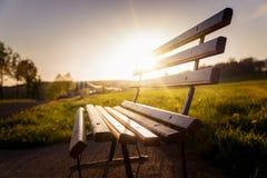 Parkera bänken på solnedgången i Autum royaltyfri bild