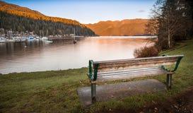Parkera bänken som förbiser den djupa lilla viken, i norr Vancouver royaltyfri bild