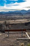 Parkera bänken som förbiser steniga berg arkivfoto