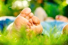 Barn kopplar ihop att ligga på gräs arkivbild