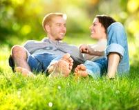 Barn kopplar ihop att ligga på gräs Arkivfoton