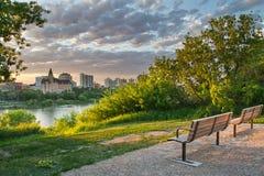 Parkera Brench och staden på solnedgången arkivfoton
