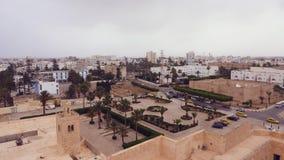 Parkera, den stora moskén och vägen med bilar i den Monastir staden, Tunisien, flyg- sikt stock video