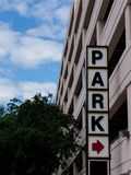 Parkera tecknet f?rutom ett parkeringsgarage arkivfoto