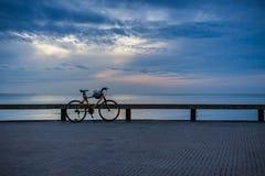 Parkerad cykel längs en strandpromenadräcke Arkivbild