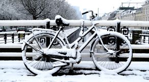 Parkerad cykel på en vinterdag i staden royaltyfri bild