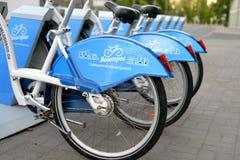 Parkerade cyklar av stadscykelhyra Arkivfoto