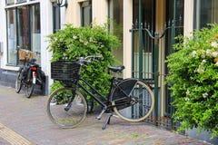 Parkerade cyklar nära de gamla husen på den smala gatan Arkivfoto