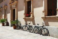 Parkerade cyklar nära en byggnad i Alcudia Royaltyfria Bilder